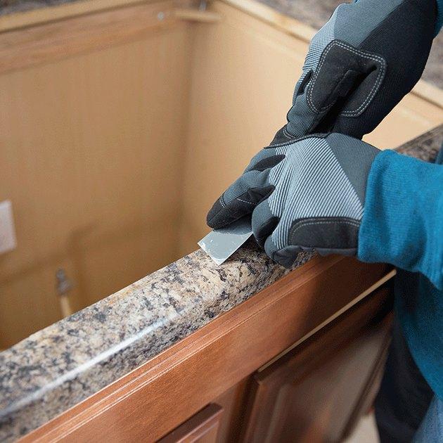 Scraping caulk from countertop.