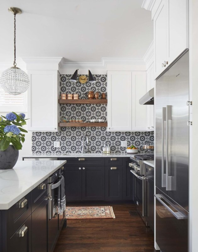black kitchen backsplash with patterned tile and black cabinets and wood flooring