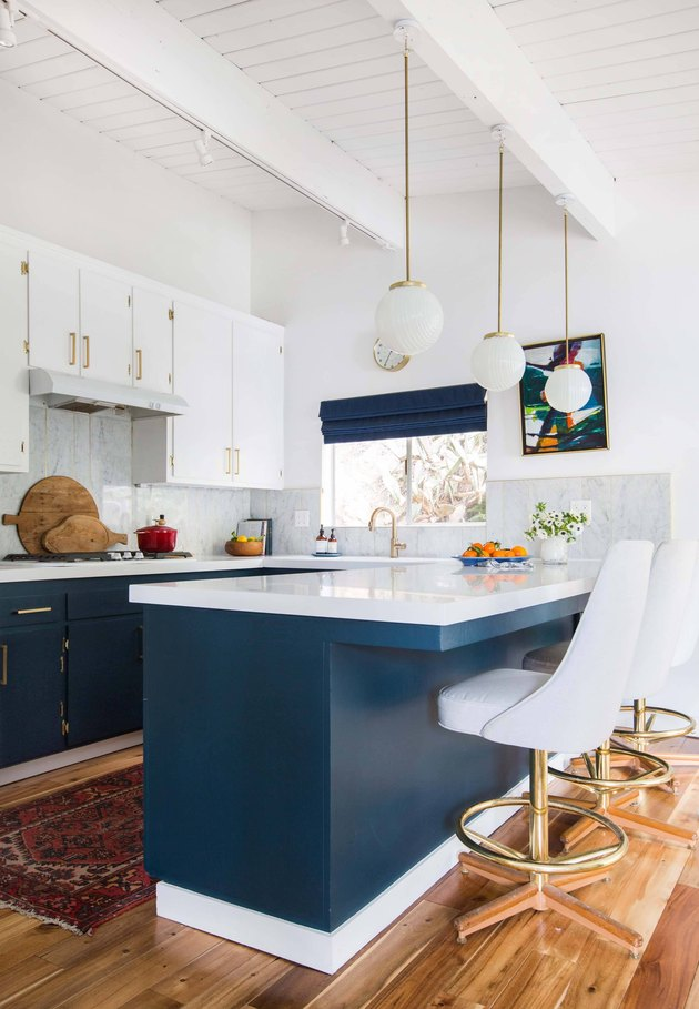 Midcentury modern style kitchen with blue cabinets and counter stools