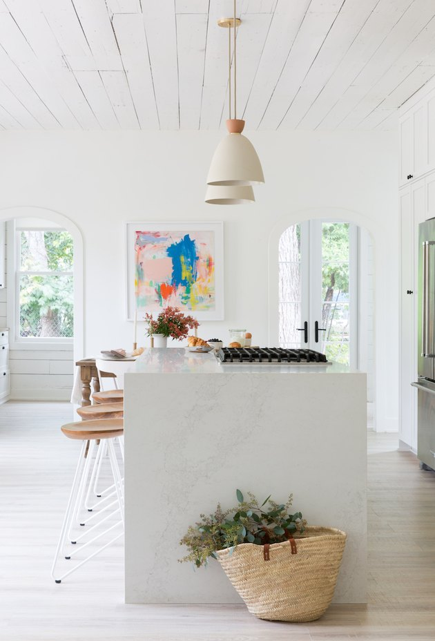 small kitchen island idea in white space with built-in stovetop and pendant lighting