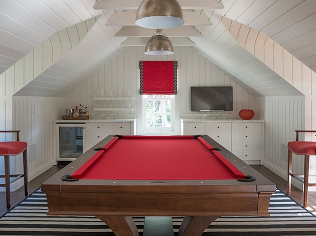attic game room with red pool table, red stools, red window shade, white shiplap walls and ceiling, metal pendant lamps, black and white striped rugs, flat screen, built-in cabinets.