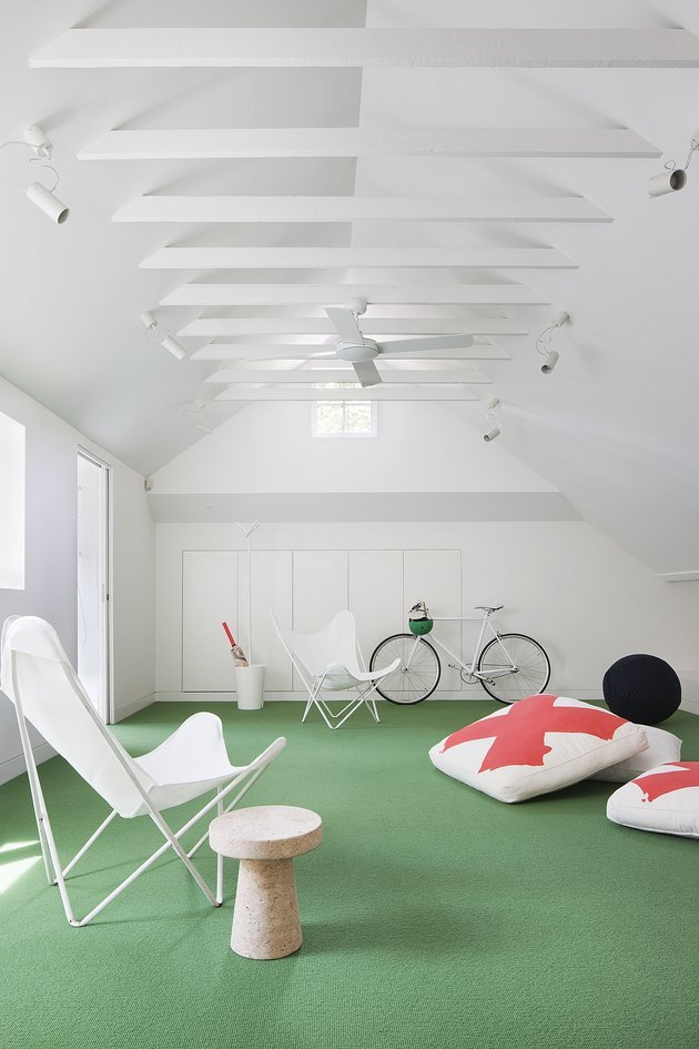 White attic game room with green astro turf, white canvas butterfly chairs, orange and white floor cushions, bicycle, end table, ceiling fan.
