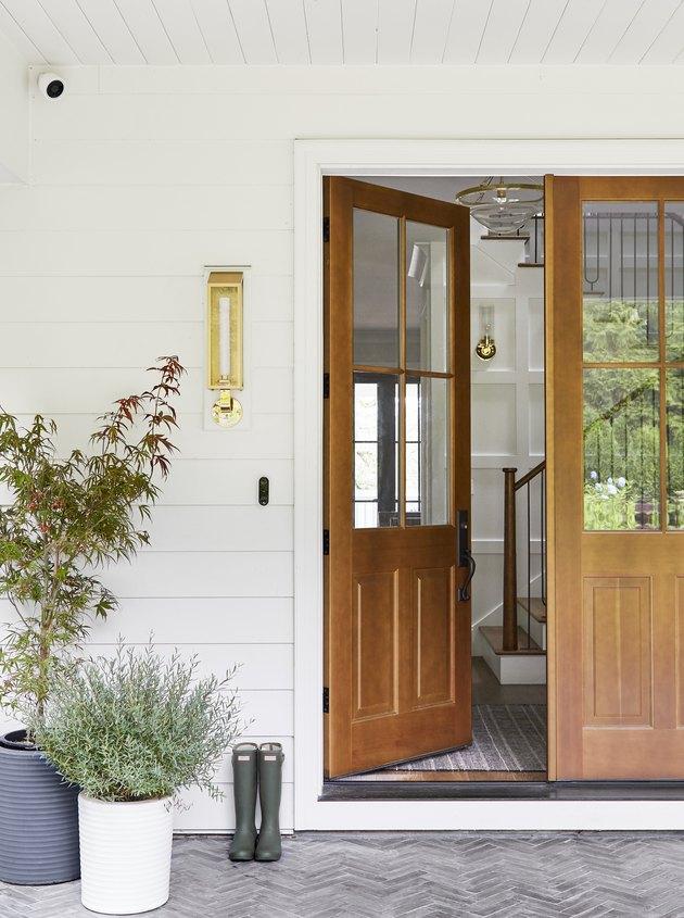 Exterior house light in brass next to wood front door