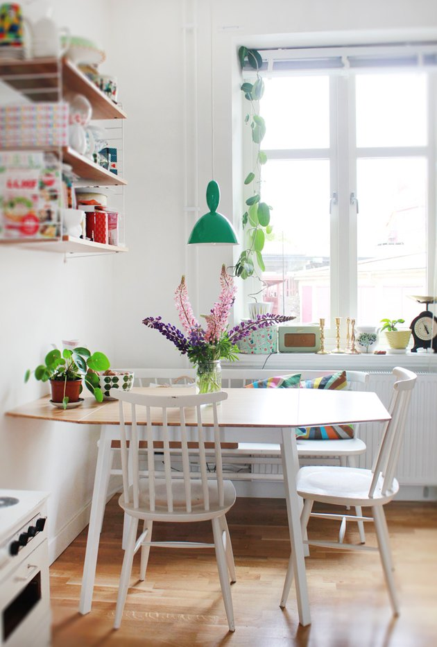 small kitchen table idea with white dining chairs and green pendant light