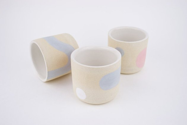 three multicolored ceramic mugs