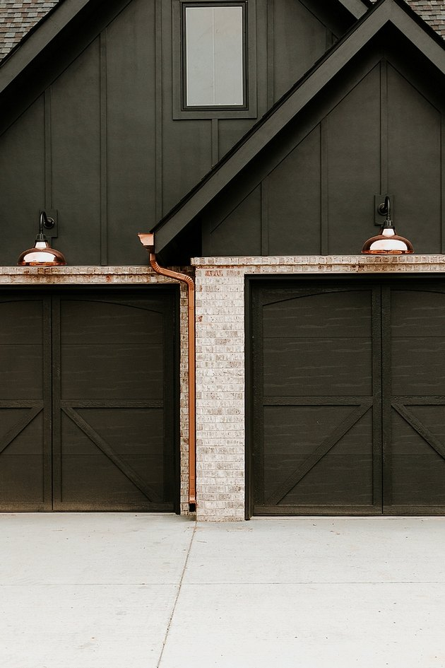 black garage doors on black home exterior with copper wall sconces