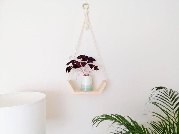 Wooden hanging shelf with macrame hanger and half-hexagonal wooden shelf