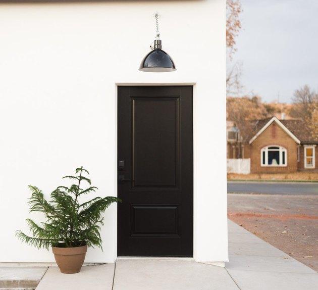 Black exterior house light on white exterior above black door