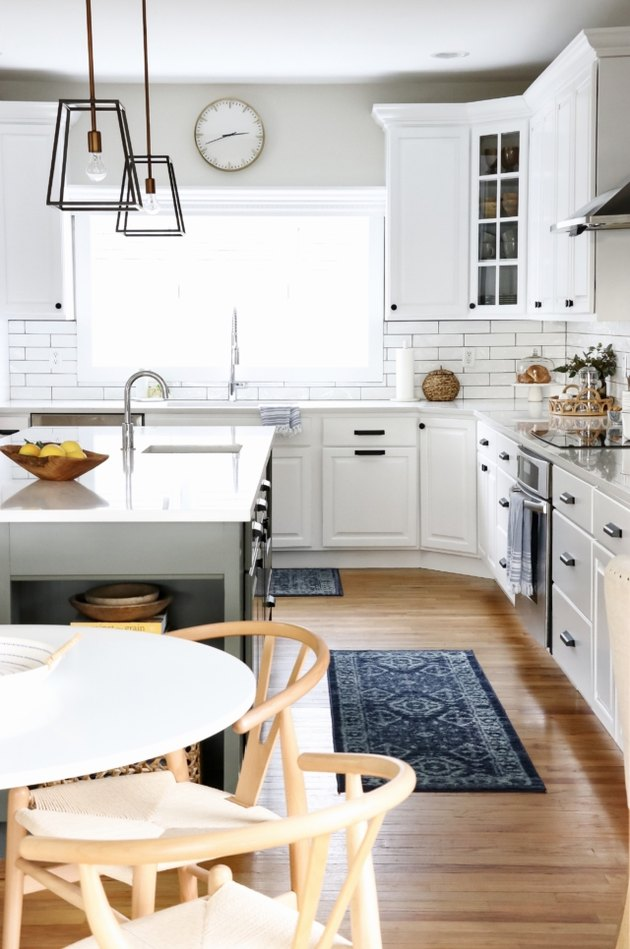 Lantern-style budget kitchen lighting with white cabinets an island with sink