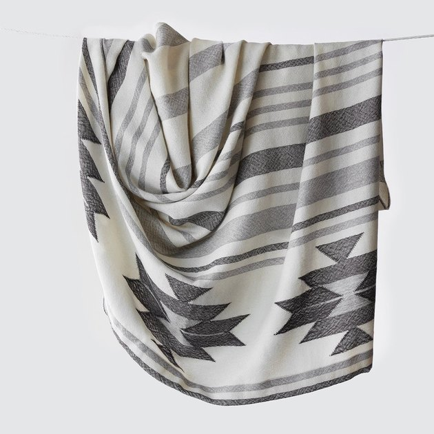 Geometric throw blanket featuring white and multiple shades of gray