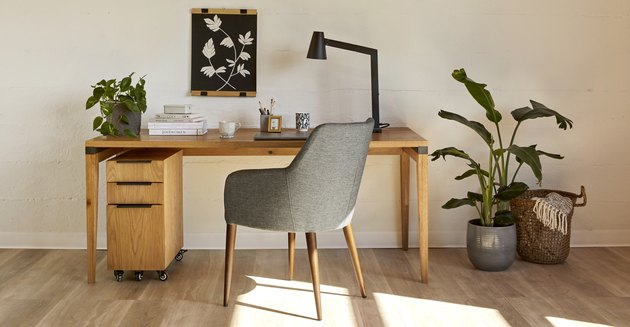 desk with gray chair and plant nearby