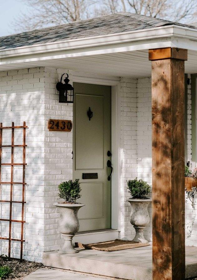 Lantern-style exterior house light on white brick exterior next to front door