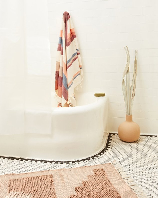 tub with towel and plant nearby