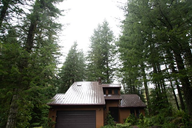 The three story chalet surround by woods.