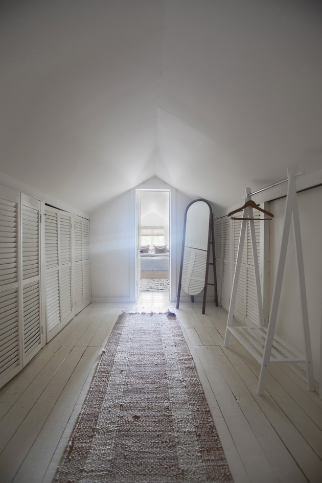 Attic Closet Ideas with standalone clothing rack and vintage runner