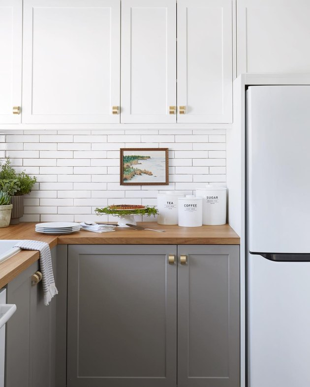 two-tone cabinet kitchen trend in 2019 with white subway tile backsplash and wood countertops