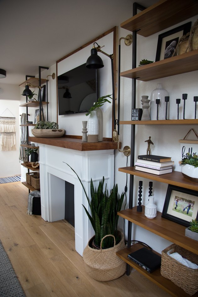 Wood and metal shelves, fireplace, wood floors, basket, plant, and flat screen in industrial basement