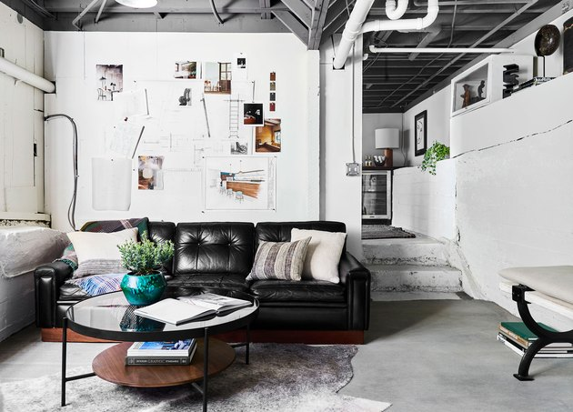 White walls, concrete floors, black leather couch, exposed ceiling, round coffee table, and cowhide rug in industrial basement
