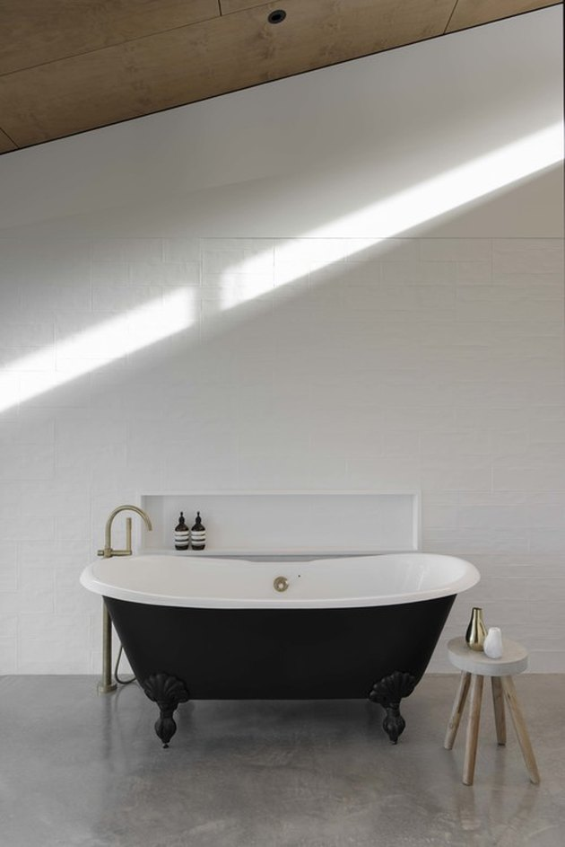 A black bathtub on concrete floors