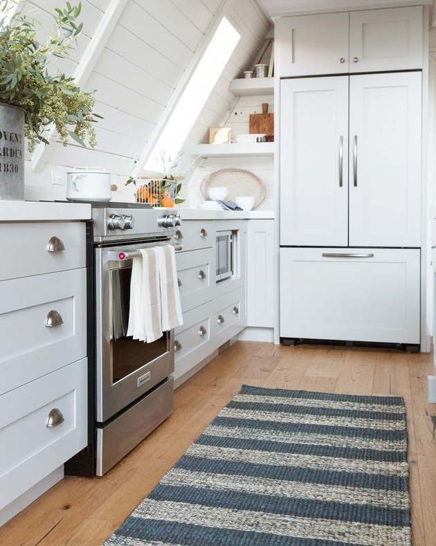 white attic kitchen with rug and stainless steel stove