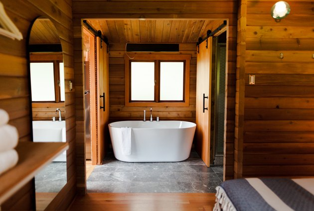 stand alone tub surrounded by natural wood and stone