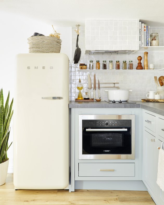 small kitchen storage idea with basket above refrigerator and open shelving