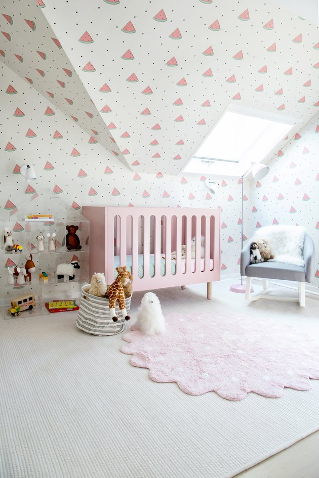 Attic skylight designs in nursery with wallpaper and pink crib