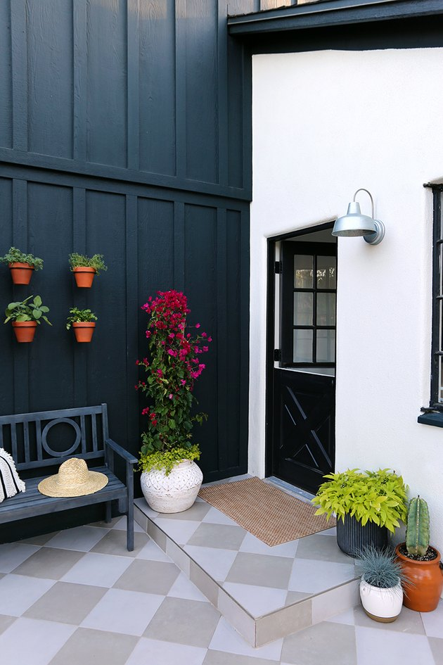 black Dutch exterior back door on white house with black siding