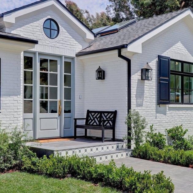 exterior door trim on white brick house with blue door and trim