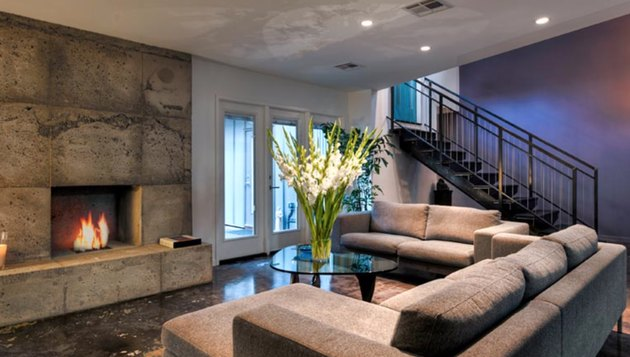 Concrete mantel, concrete floors, gray couches, fireplaces, stairway, large vase with flowers in industrial basement