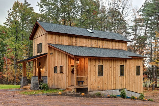 Board and batten exteriors on wood cabin with black roof