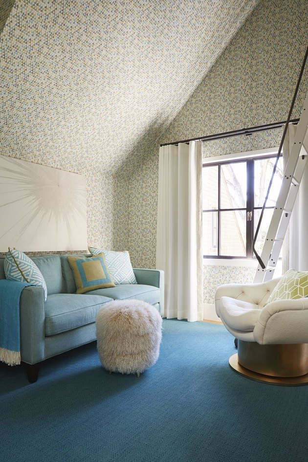 attic living room with blue sofa, rug, wallpaper and sheepskin pouf