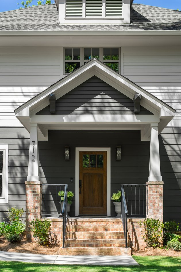 exterior door trim on gray and white house with wooden door and white trim