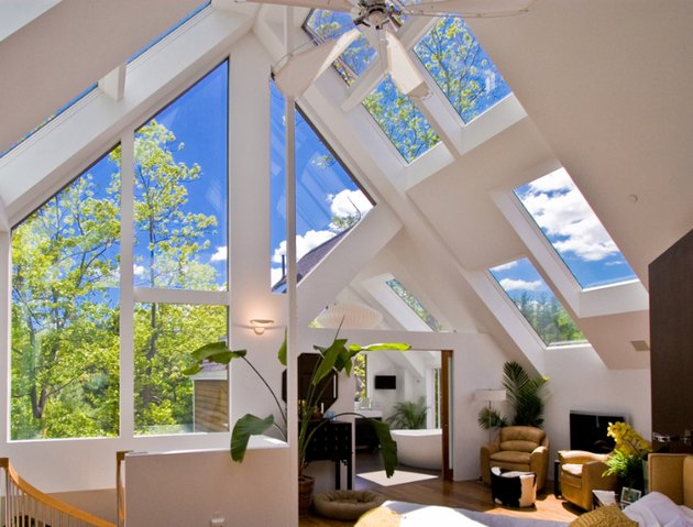 attic skylight designs in white attic with multiple windows and plants