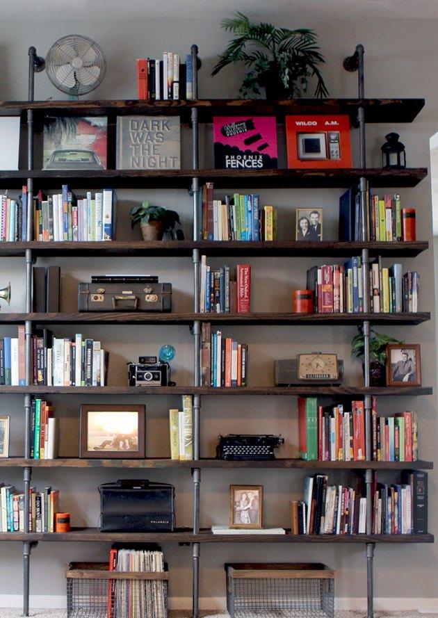 floor to ceiling pipe and wood DIY industrial bookshelf