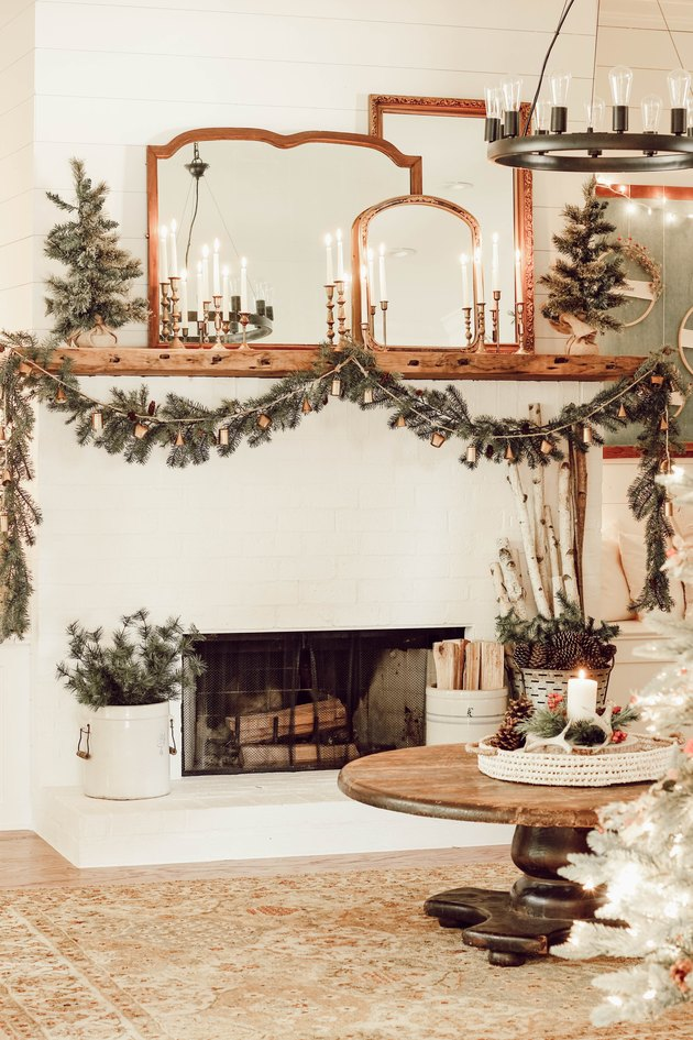 Rustic Christmas decorations with vintage pieces on mantle and winter greenery