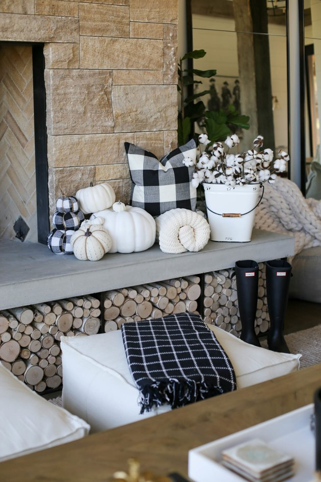 Rustic fall decor on fireplace with black and white plaid pillow and pumpkins