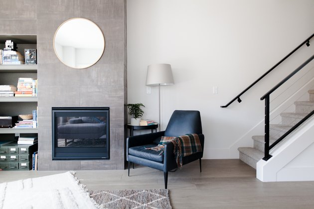 Living room with modern blue lounge chair and concrete fireplace surround