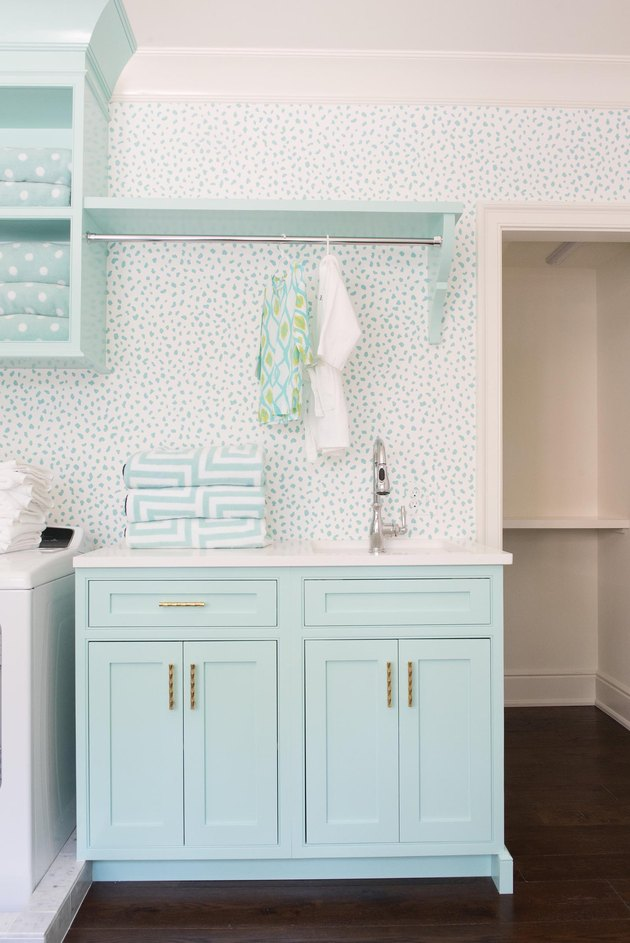 laundry room with sporty wallpaper and aqua color cupboards