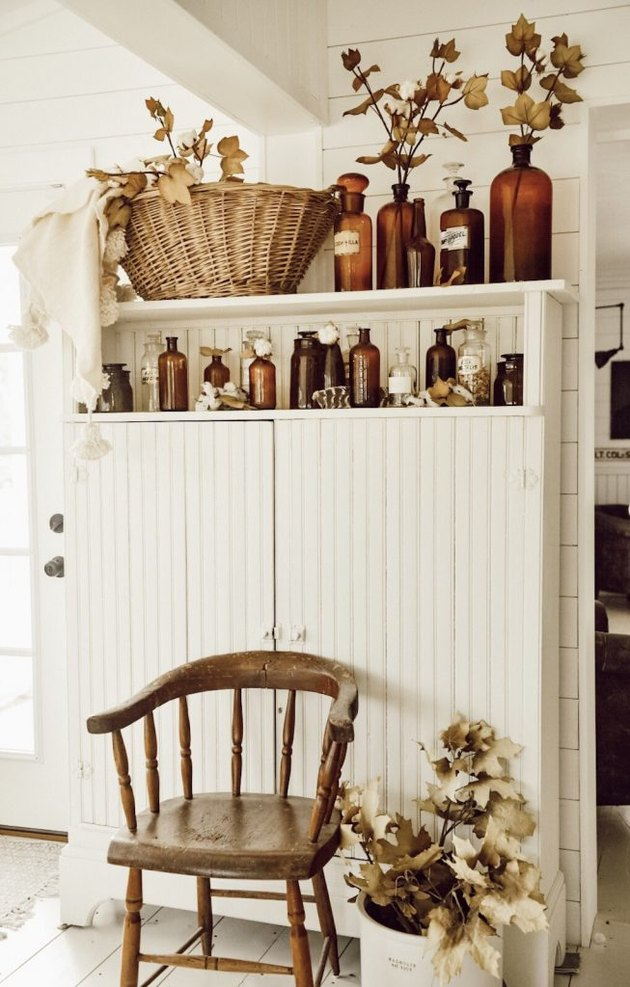 Rustic fall decor with vintage amber bottles and vintage white hutch