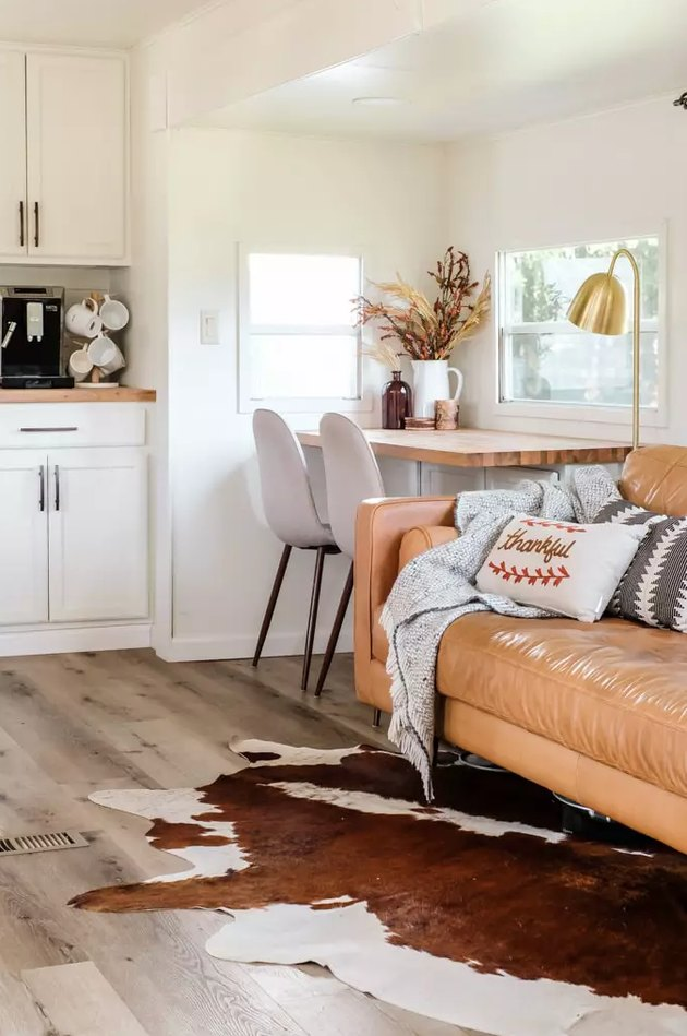 Rustic fall decor with leather couch and cowhide rug in RV