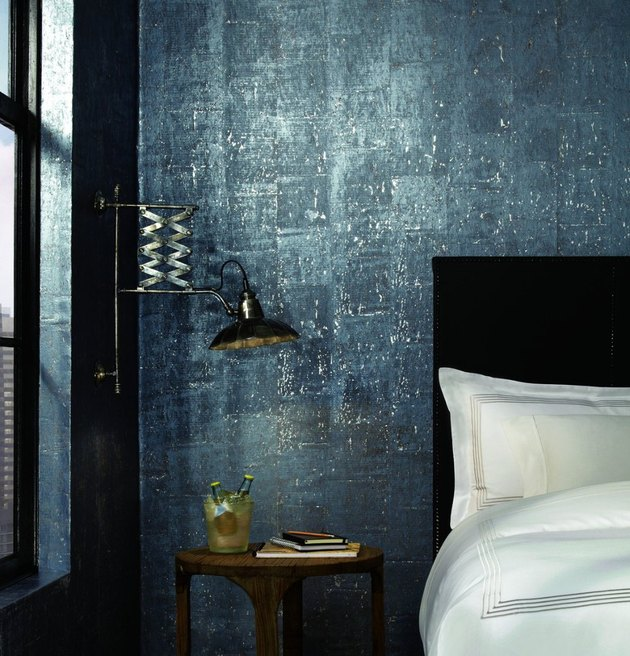 blue cork industrial wallpaper behind a bed