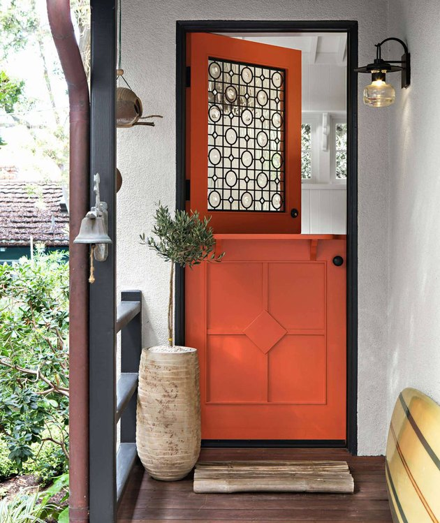 orange exterior Dutch door with intricate glass pane