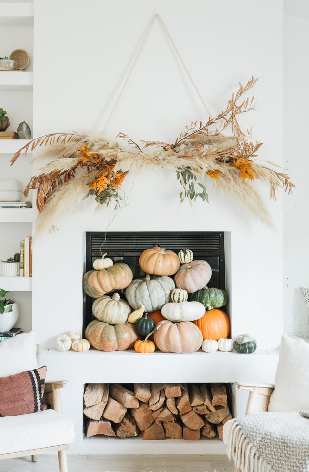 Rustic fall decor on fireplace mantle with natural wall hanging and pumpkins
