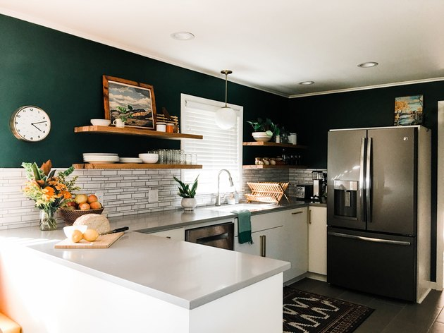 Dark green walls in an otherwise white and gray kitchen