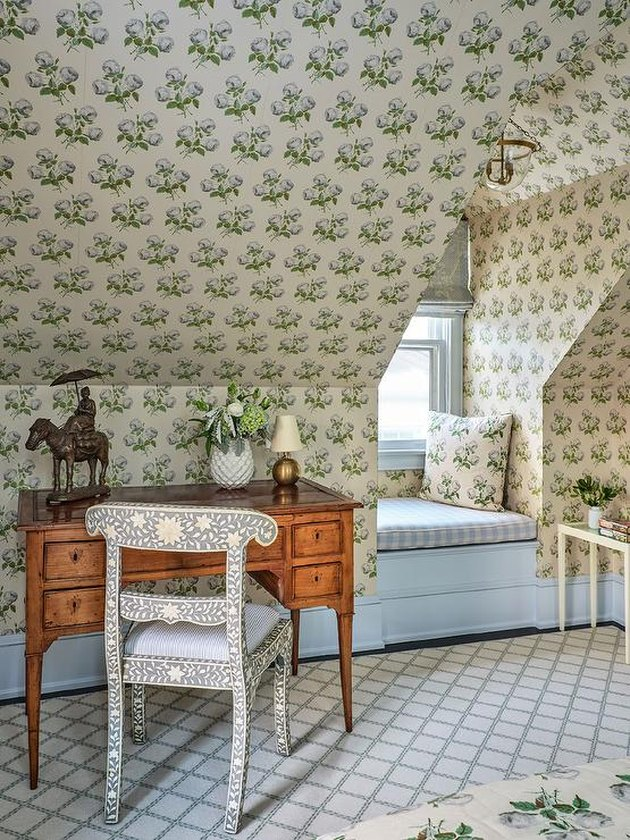 Small attic ideas for a room with a complex wallpaper pattern and study desk.