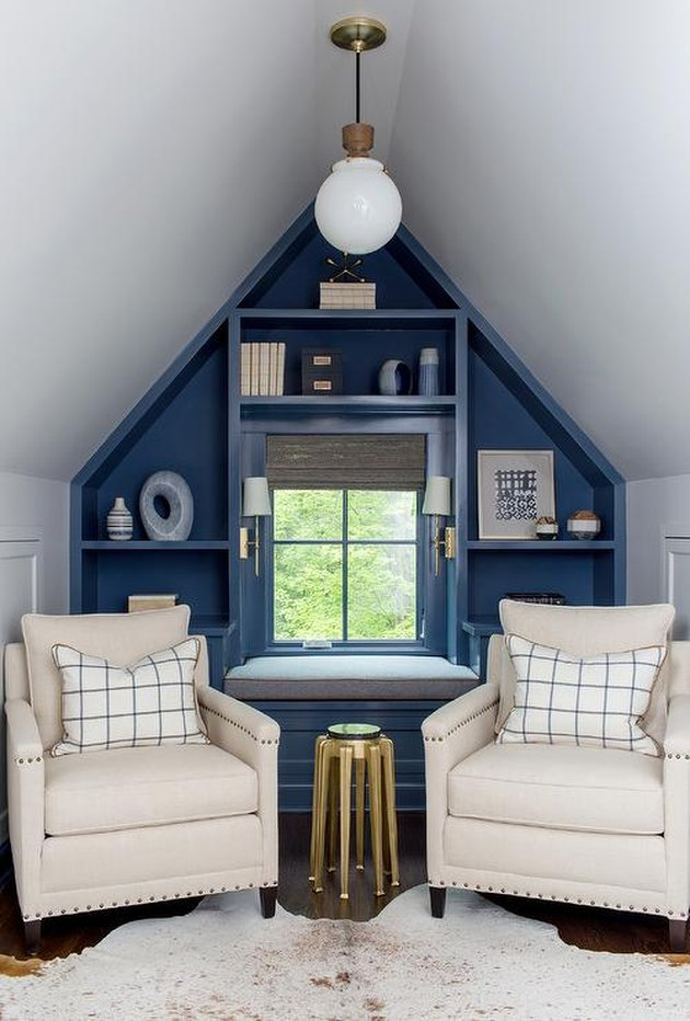 Small attic ideas with blue accent wall and two white fabric armchairs.