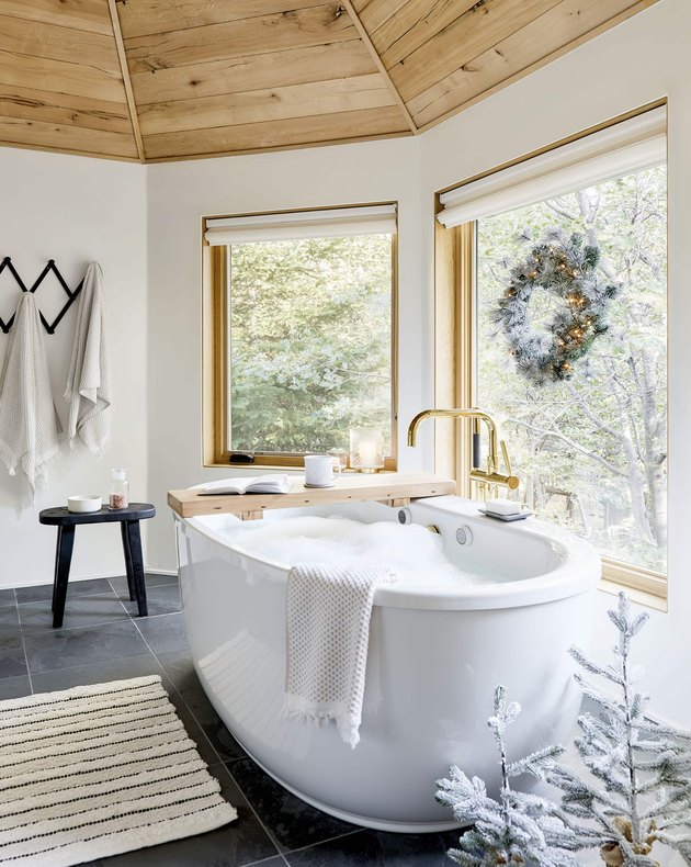 white bathroom with big tub and Christmas window decorations