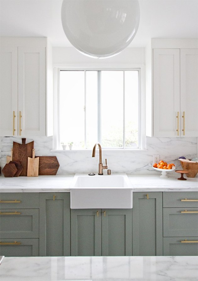 Brass hardware in a mint-and-white kitchen
