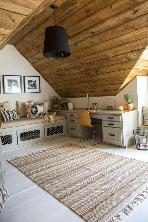 rustic attic office idea with wood ceiling and built-in seating